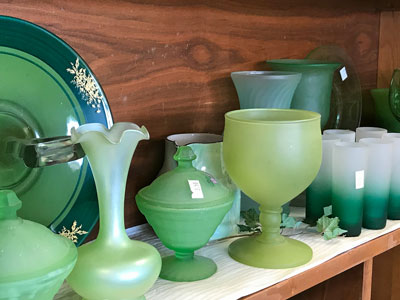 green glassware and vases at an estate sale